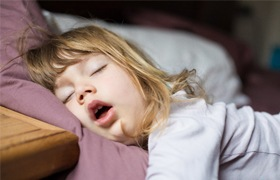 A little girl asleep with her mouth open