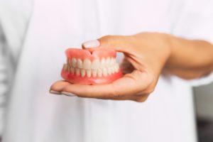 doctor holding dentures in Casper