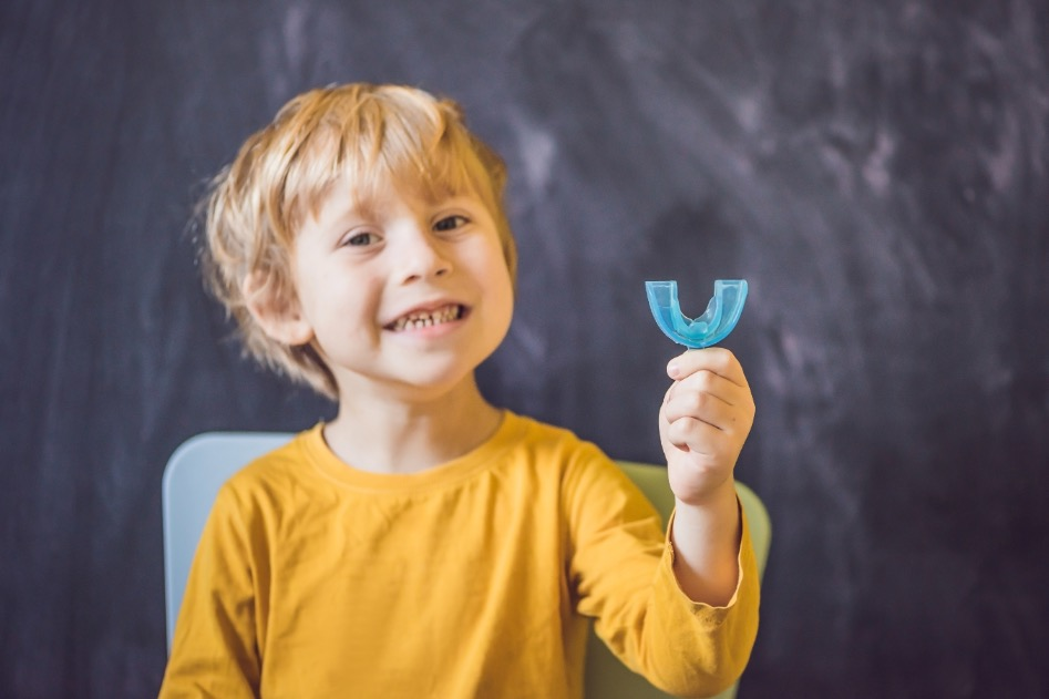 Child holding a blue mouthpiece