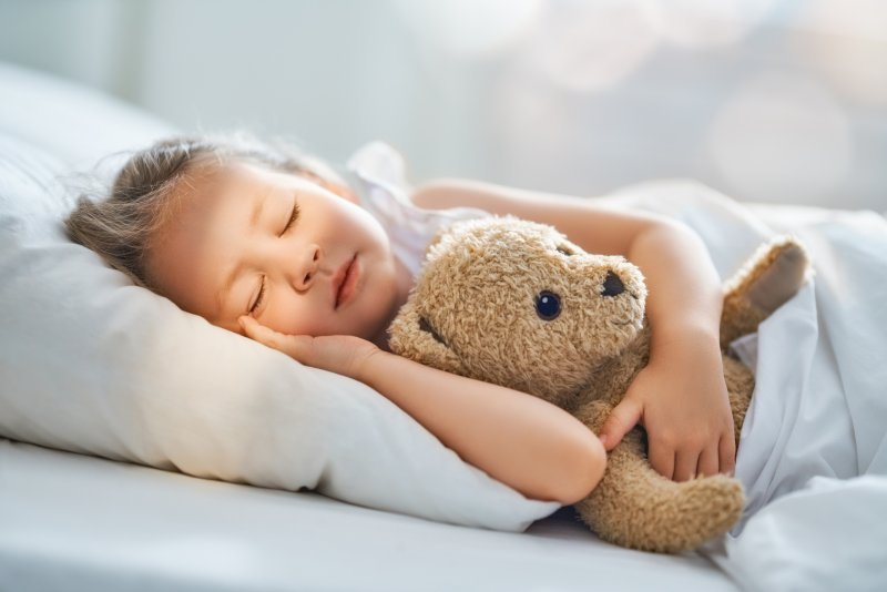a little girl in bed holding her teddy bear and sleeping