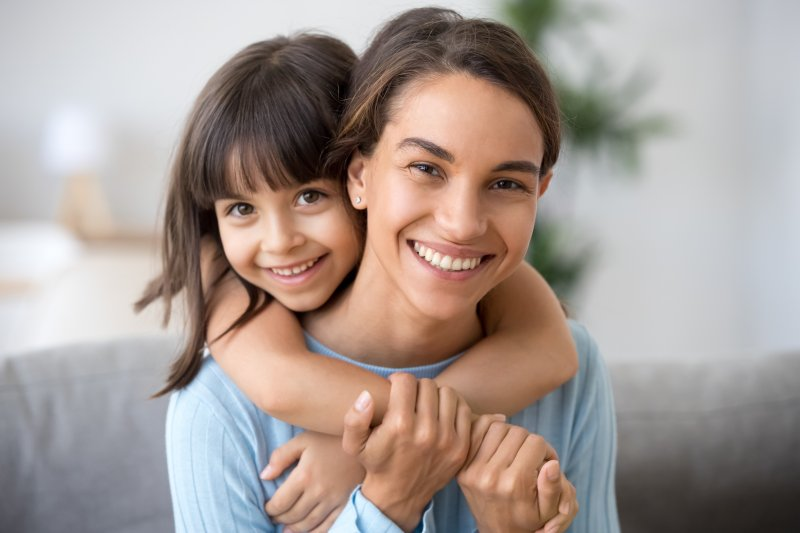 a little girl hugging a young woman from behind with her arms crossed around the woman's neck and shoulders