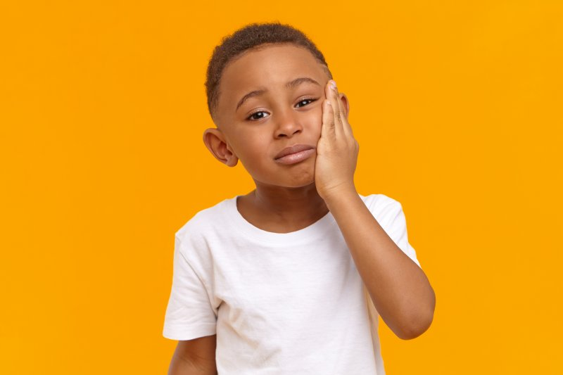 a little boy wearing a white t-shirt and holding his jaw because of increased pain